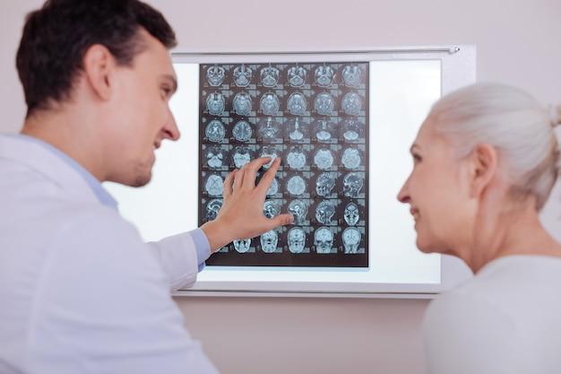 Médico bonito e positivo olhando para sua paciente e sorrindo enquanto lhe contava as boas notícias