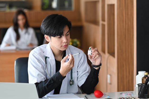 Médico bonito segurando a seringa e o frasco da vacina. conceito de medicina e saúde.