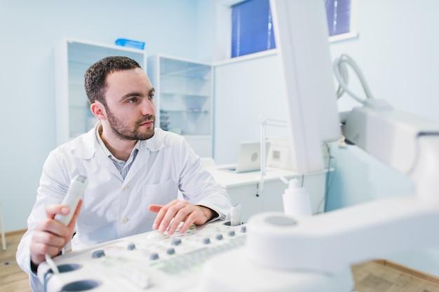 Médico bonito usando uma máquina de ultrassom