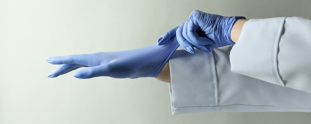 Médico calçando luvas médicas cinza claro