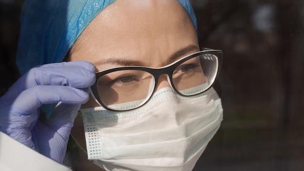 Médico cansado corrige óculos, olhando para a janela