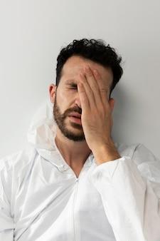 Médico cansado de tiro médio usando terno de material anti-risco