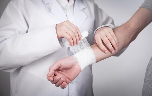 Médico caucasiano colocando curativo na mão do paciente.