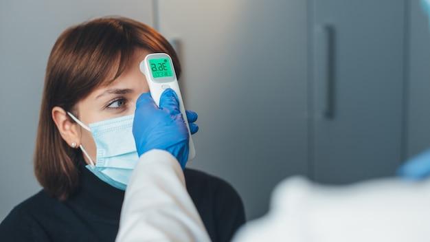 Médico caucasiano de luvas mede a temperatura corporal do paciente com máscara durante uma consulta