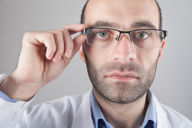 Médico caucasiano de óculos, olhando para a câmera.