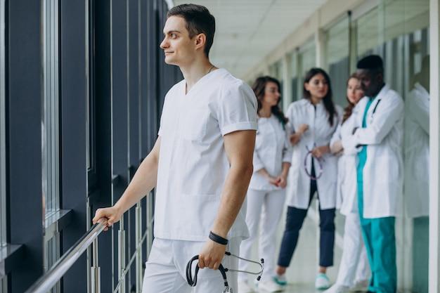Médico caucasiano homem parado no corredor do hospital