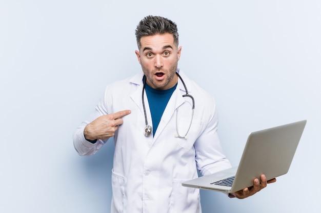 Médico caucasiano homem segurando um laptop surpreendeu apontando para si mesmo, sorrindo amplamente.