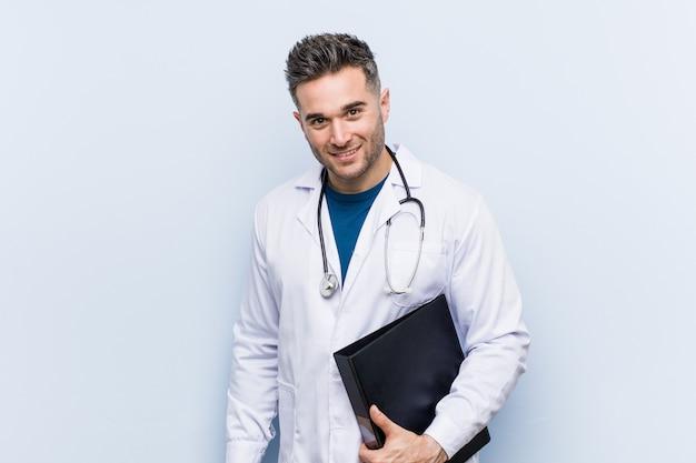 Médico caucasiano homem segurando uma pasta feliz, sorridente e alegre