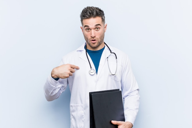 Médico caucasiano homem segurando uma pasta surpreendeu apontando para si mesmo, sorrindo amplamente.