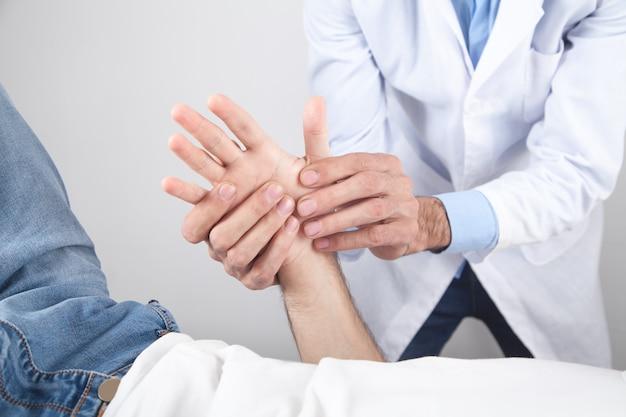 Médico caucasiano massageando a mão do paciente.