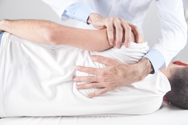 Médico caucasiano massageando o ombro do paciente