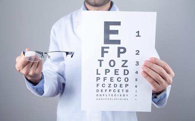 Médico caucasiano mostrando óculos e teste de exame oftalmológico.