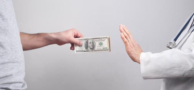 Médico caucasiano, recusando dinheiro do paciente.