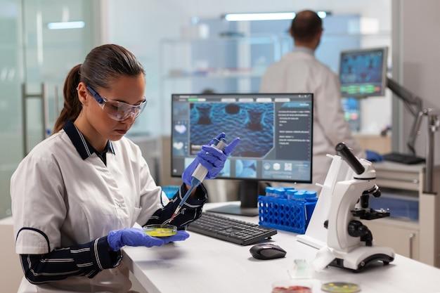 Médico cientista conduzindo experimento clínico usando micropipeta