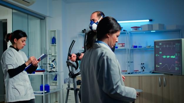 Médico cientista do esporte olhando para o monitor com leitura de ekg enquanto homem com máscara correndo no aparelho elíptico monitorando sua resistência