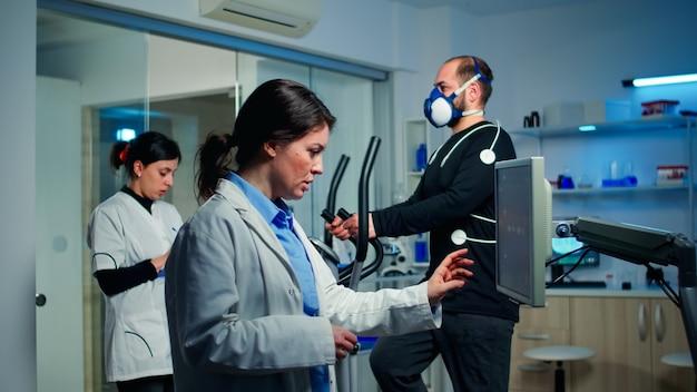 Médico cientista do esporte verificando a varredura de ekg no monitor e discutindo enquanto um homem com máscara correndo no cross trainer monitorando sua resistência