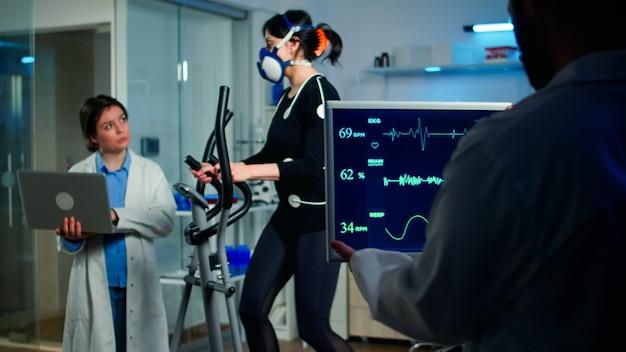 Médico cientista segurando um laptop e controlando dados de ecg exibidos em monitores de laboratório