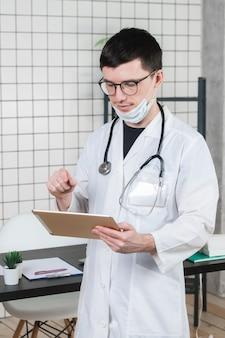 Médico cirurgião com computador tablet no escritório do hospital.