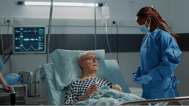 Médico cirurgião de enfermaria de hospital falando com paciente doente