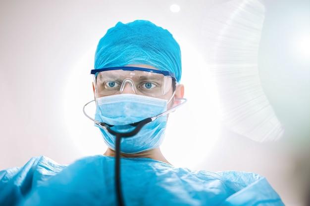 Médico cirurgião na sala de cirurgia olhando para a câmera