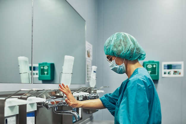 Médico cirurgião profissional lava as mãos em uma sala especial antes da operação.