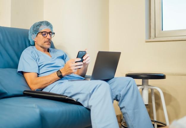 Médico cirurgião usando laptop e telefone celular após a operação