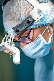 Médico cirurgião usando máscara protetora e chapéu durante a operação