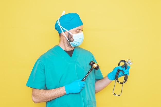 Médico cirurgião vestido com uniforme de sala de operação com estetoscópio em uma mão e martelo do juiz na outra.