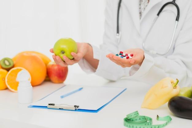 Médico close-up com pílulas e frutas frescas
