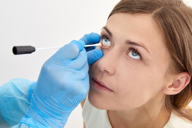 Médico colhendo amostra com cotonete do olho em busca de bactérias e vírus