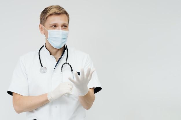 Médico coloca luvas e usa máscara médica