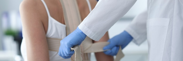 Médico colocando espartilho nas costas de paciente feminino closeup