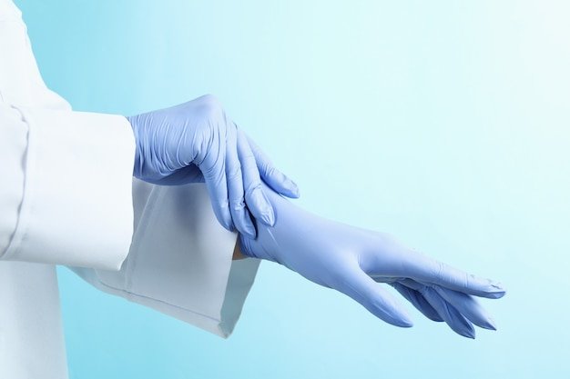 Médico colocando luvas médicas em azul