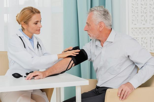 Médico colocando manguito de pressão arterial