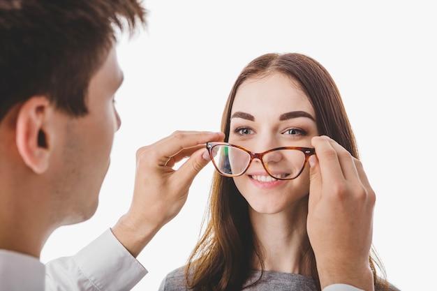 Médico colocando óculos sobre mulher