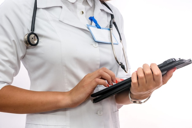 Médico com área de transferência. mulher bonita em uniforme médico segurando uma prancheta isolada no branco