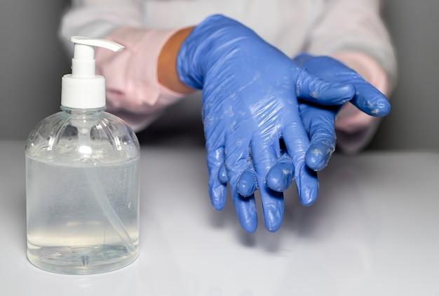 Médico com as mãos em luvas azuis, limpeza e lavagem das mãos com desinfetante na garrafa, close-up.
