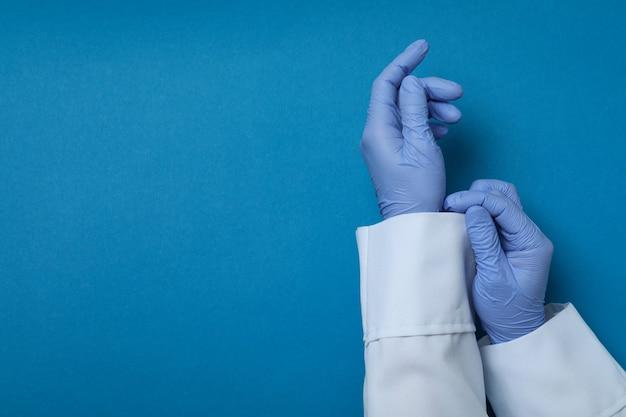 Médico com as mãos em luvas médicas sobre fundo azul isolado