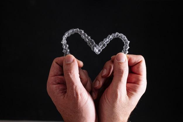 Médico com as mãos segurando alinhadores dentais transparentes em forma de coração
