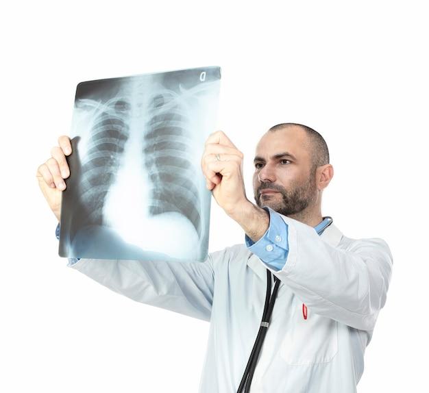 Médico com barba e vestido examina uma radiografia de tórax