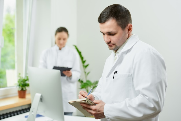 Médico com caderno e caneta