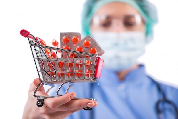 Médico com carrinho de compras cheio de pílulas isoladas no branco