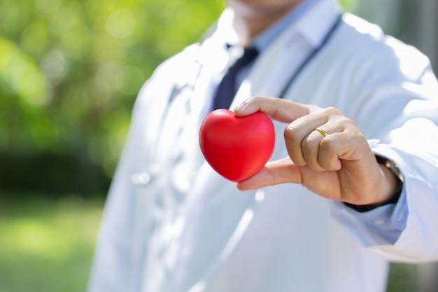 Médico com coração vermelho sobre fundo natural