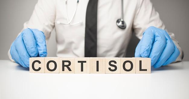 Médico com cubos de madeira nas mãos com o texto cortisol