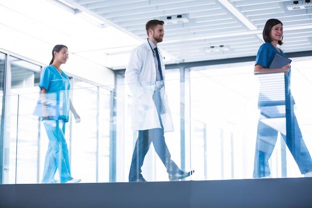 Médico com enfermeiros andando no corredor