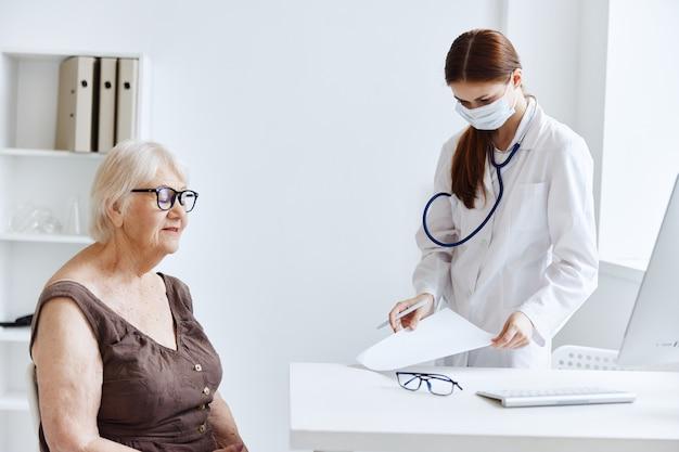 Médico com estetoscópio de máscara médica em mãos, diagnósticos profissionais