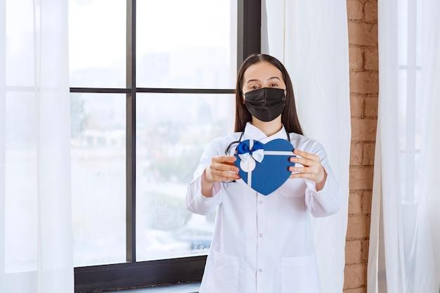Médico com estetoscópio e máscara preta segurando uma caixa de presente em forma de coração azul.
