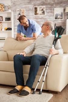 Médico com estetoscópio na casa de repouso, falando com o velho. homem com muletas.