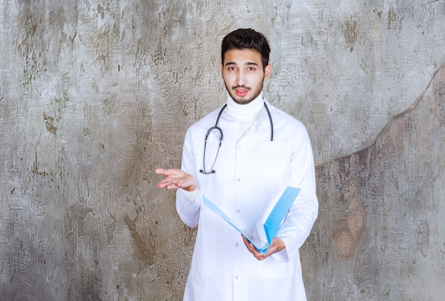 Médico com estetoscópio segurando uma pasta azul e interagindo com a pessoa ao redor.