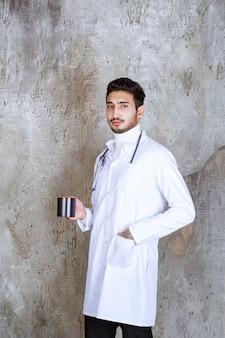 Médico com estetoscópio segurando uma xícara de café.
